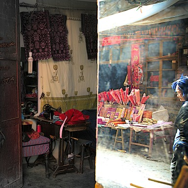 At the old Kaili market, a shopkeeper's mirror reflects the movement of the day.