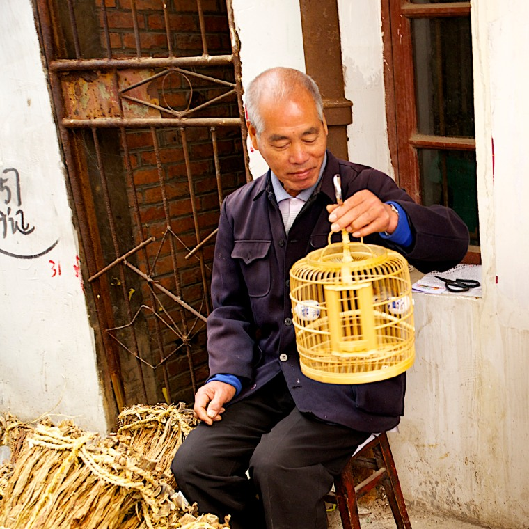 A tobacco seller at the old Kaili market spins his songbird's cage as he awaits customers.