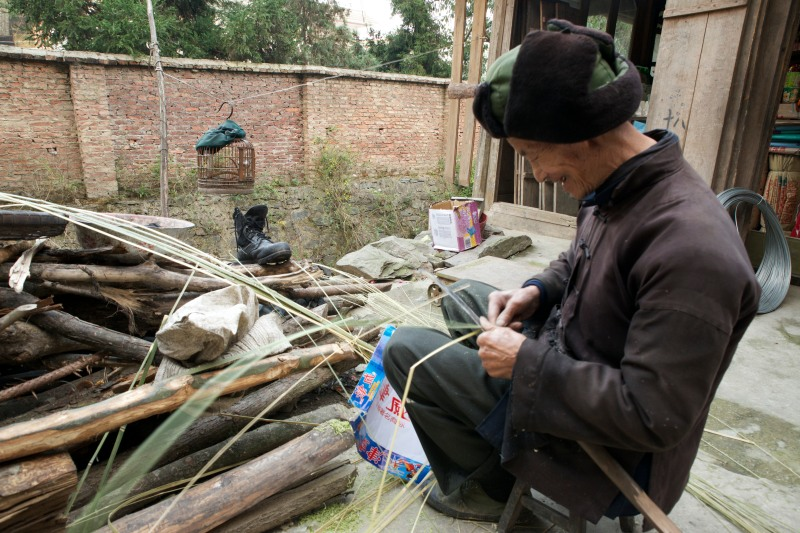 A man whistles with his songbird as he splits reeds in the village of Bengli, China.