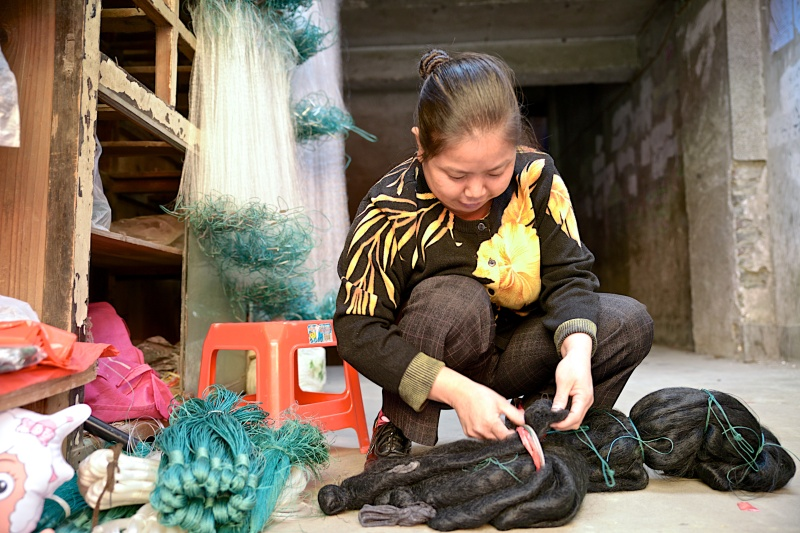 In China, a shopkeeper strings up hair to sell along with her fishing nets.