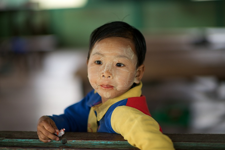 A boy finishes his candy before the teacher arrives in Kazat, Myanmar.
