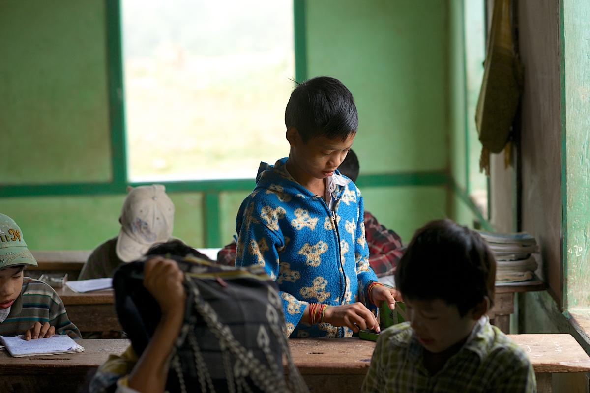 A boy rearranges his school box in Kazat, Myanmar.