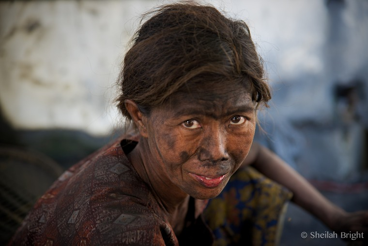 On Mandalay's infamous Marble Street, a woman sells coal in a cloud of white dust.