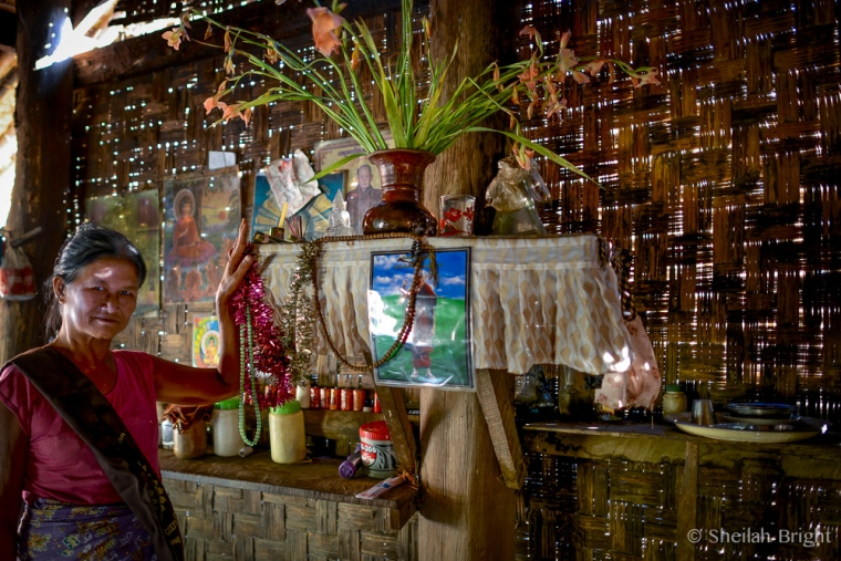 A Burmese woman shows off the shrine in her home.