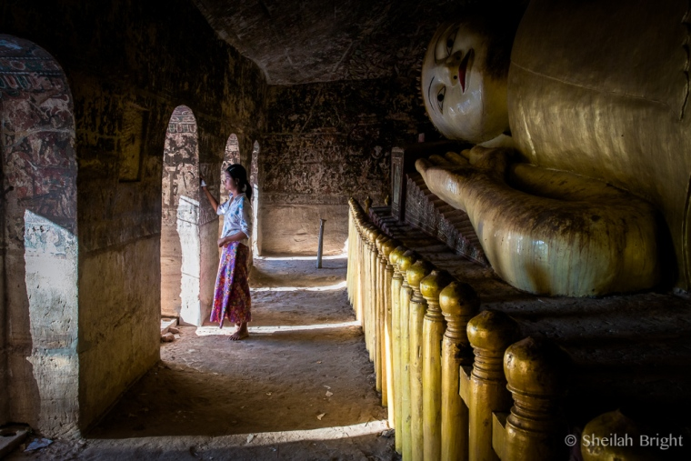 A local girl pauses in a doorway after visiting a reclining Buddha in Shwe ba daung