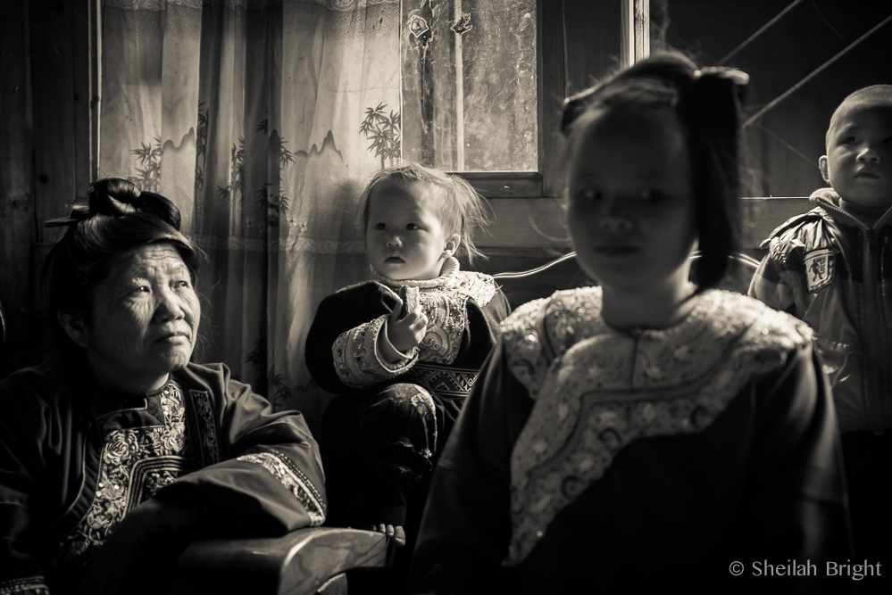 In the Bengli village in southwestern China, a grandmother watches her granddaughter as she prepares to marry.