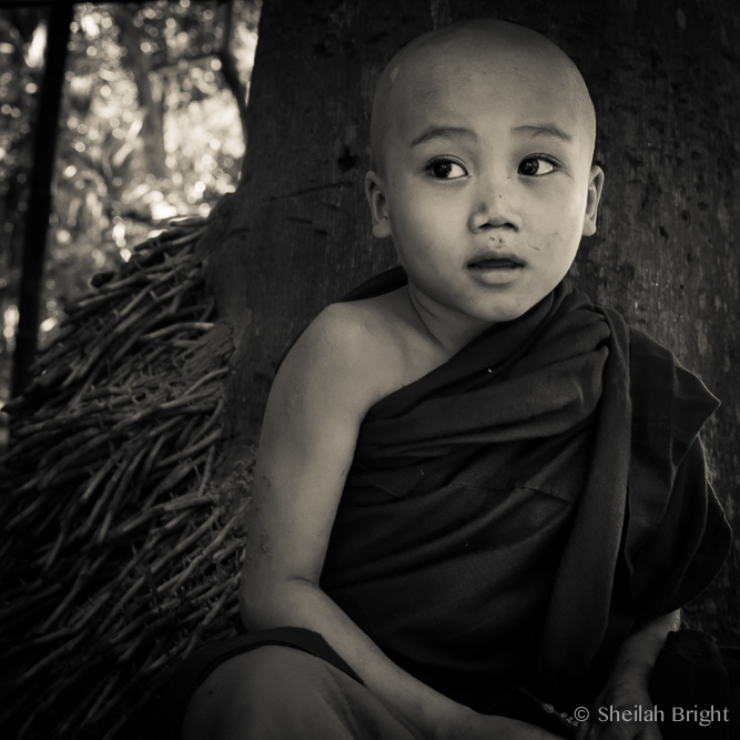 A young boy takes a break against a tree near Mandalay, Myanmar.