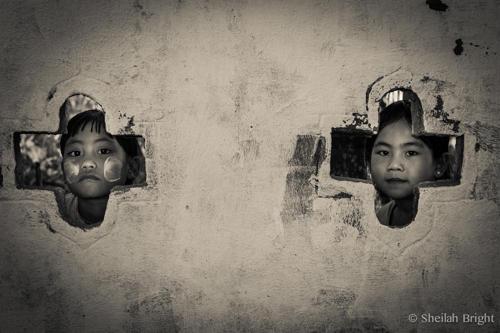 In the Nan Yin village in Myanmar, schoolchildren peak from ancient walls surrounding the monastery.
